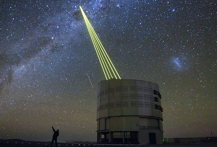 A watchtower in the desert that connects to a satellite at night. Next to it is a man with a camera