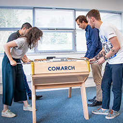 Four young people play foosball