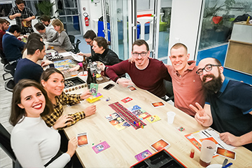 A group of young and smiling people play a board game