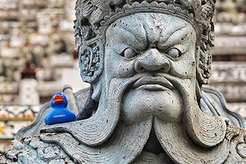 A Thai sculpture with a rubber duck with the company logo on it