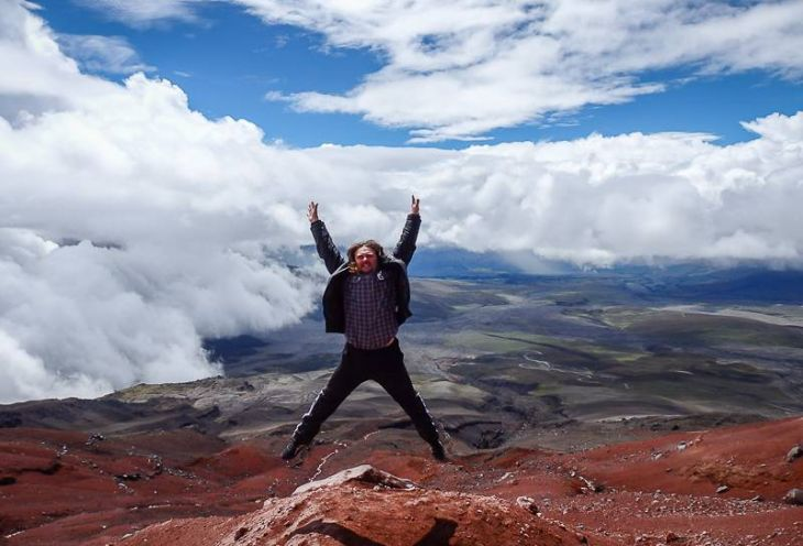 A man jumping while posing for pictures in the mountains in South America