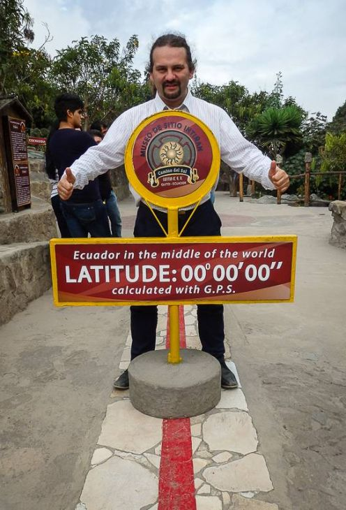 The man posing for the photo on the equator in Ecuador